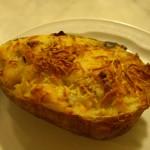 巨大ジャガイモの半分をくりぬいてベシャメルソースや生ハムとあわせてチーズをのせてオーブンで焼いたもの。
