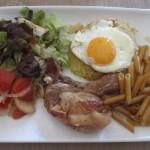 骨付き豚肉のステーキ、パスタ、ジャガイモのガレットに目玉焼き、サラダ。